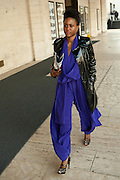 A woman in a blue jumpsuit leaves the show.