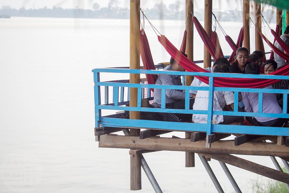 Vanaf een restaurant kijken gasten uit op .de Mehkong, de grootste en belangrijkste rivier in Cambodja.