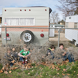 Kids hide near a chain link fence while participating in a game of hide and seek during lunch recess at Owyhee-Harbor Elementary School. Friday February 27, 2015