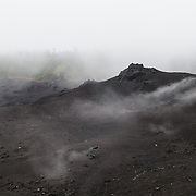 Steam rising from the warm ground mixes with clouds at the summit of Pacaya Volcano in Guatemala. Pacaya is an active volcano that forms part of the Central America Volcanic Arc. It forms a popular tourist destination easily accessible from Antigua and Guatemala City. Situated within the Pacaya National Park, it rises to 2,552 metres (8,373 ft). Its last major eruption, which caused considerable damange to nearby villages and reshaped the summit, was in May 2010. That eruption and scattered volcanic ash over much of the nearby area, prompting school closings and emergency evacuations and cleared much of the vegetation near the top of the mountain.