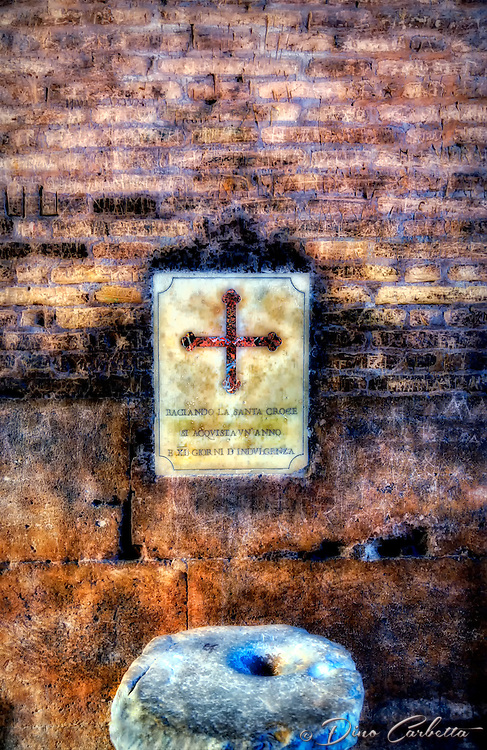 """""""Kissing the Holy Cross is acquired one year and 40 days of indulgence""""…<br /> <br /> <br /> The title of this image is the inscription on each cross placed at every entrance to the Colosseum.  It still maintains close connections with the Roman Catholic Church, as each Good Friday the Pope leads a torch lit """"Way of the Cross"""" procession that starts in the area around the Colosseum.  The Colosseum is generally regarded by Christians as a site of the martyrdom of large numbers of believers during the persecution of Christians in the Roman Empire, as evidenced by Church history and tradition.  A Cross stands exultant in the Colosseum center with a plaque stating:  """"The amphitheatre, one consecrated to triumphs, entertainments, and the impious worship of pagan gods, is now dedicated to the sufferings of the martyrs purified from impious superstitions.""""  In viewing many historical sites during my journey in Italy, seeing the iconic Colosseum for the first time…I became awestruck.   It is as grand in person as it appears in the media, and it seems to hold a very mystical aura.  Climbing the ancient steps inside, one cannot help but feel not only the suffering of its past, but the forgiveness and sacrifice of its present stature."""