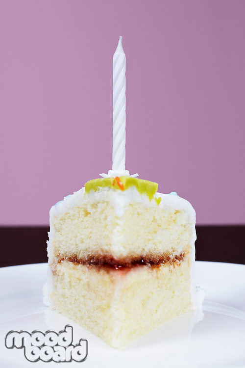Slice of cake with birthday candle, close-up