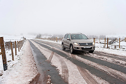 © Licensed to London News Pictures. 02/04/2018. Builth Wells, Powys, Wales, UK. A motorist drives through a wintry landscape along the B4520 (Brecon road) near Builth Wells, Powys,  on the Mynydd Epynt range at approximately 400 metres above dea-level.                          Photo credit: Graham M. Lawrence/LNP