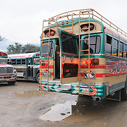Loading chicken buses behind the Mercado Municipal (town market) in Antigua, Guatemala. From this extensive central bus interchange the routes radiate out across Guatemala. Often brightly painted, the chicken buses are retrofitted American school buses and provide a cheap mode of transport throughout the country.