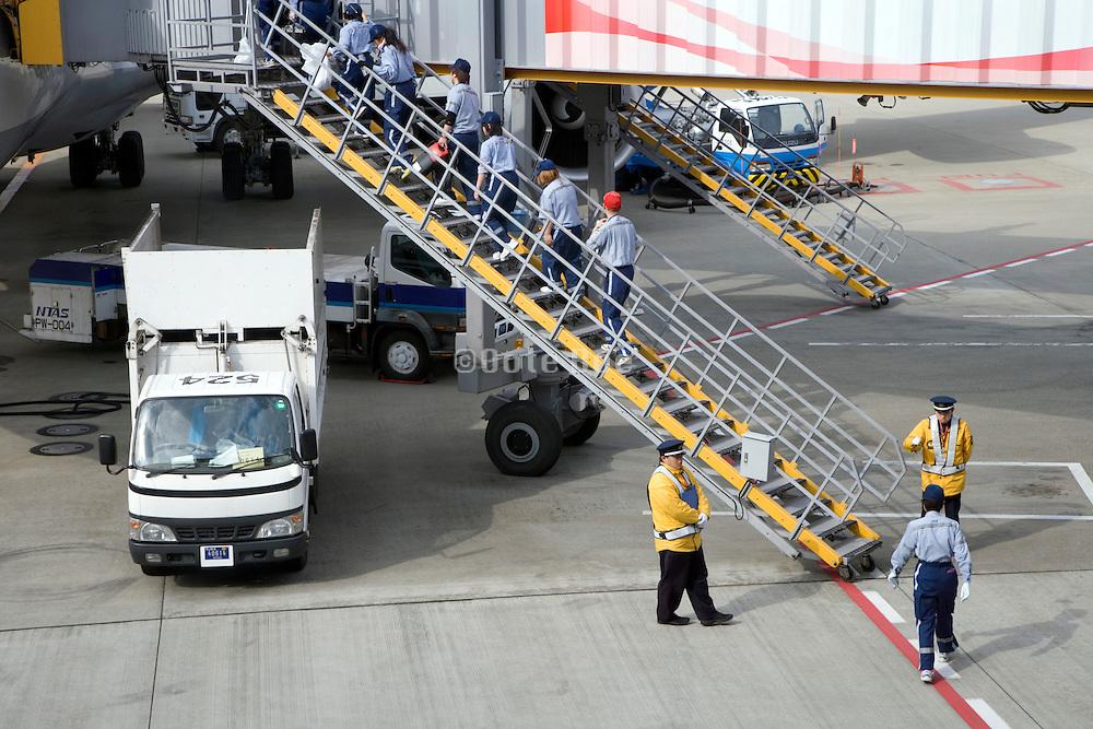 cleaning crew entering a passenger airplane at Narita International airport Tokyo Japan