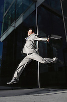 Businessman holding briefcase Jumping outside building