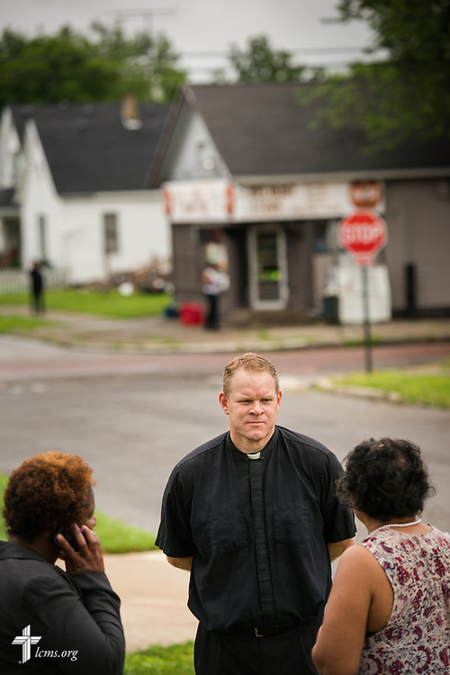 The Rev. Peter M. Burfeind, new domestic missionary and campus pastor at the University of Toledo, listens to a resident in a neighborhood along with community advocate Alicia Smith (left) on Thursday, July 9, 2015, in Toledo, Ohio. LCMS Communications/Erik M. Lunsford