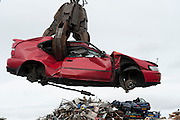 Scrap metal. A red car for scrap is grabbed by a clamp and lifted into the air at a recycling centre.<br /> Picture: Sean Spencer/Hull News & Pictures<br /> 01482 210267/07976 433960<br /> www.hullnews.co.uk   sean@hullnews.co.uk
