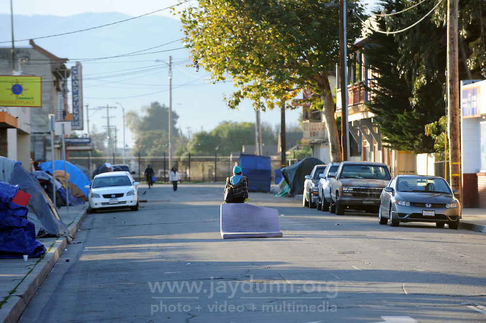 On Soledad St. in Salinas, a woman drags her mattress down the middle of the street in search of a safe place to sleep.