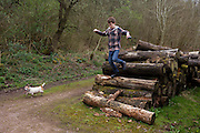 Teenage boy jumps down off a pile of logs during a countryside walk with his pet dog.