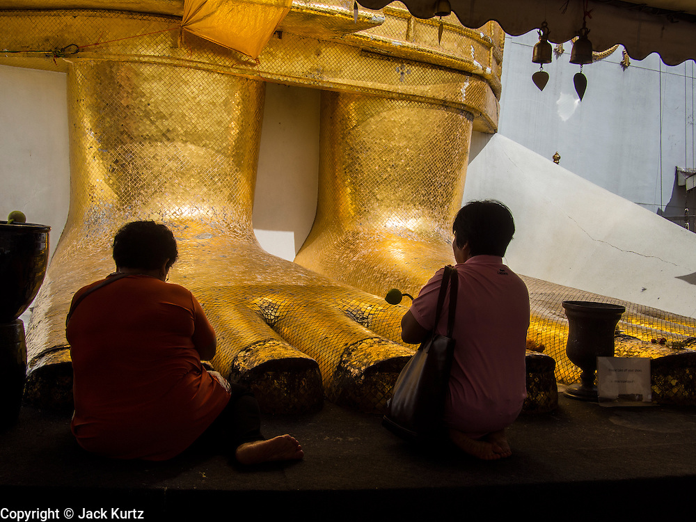 """15 AUGUST 2014 - BANGKOK, THAILAND:   People pray at the base of standing Buddha statue in Wat Intharawihan. Wat Intharawihan (also called Wat Intharavihan) is a Buddhist temple located in the Nakhon District of Bangkok, Thailand. It was built at the beginning of the Ayutthaya period and was originally called Wat Rai Phrik. The best known feature of the temple is a 32 meter high (105 feet), 10 meter wide (33 feet) standing Buddha referred to as Luang Pho To or """"Phra Si Ariyamettrai."""" It took over 60 years to complete and is decorated in glass mosaics and 24-carat gold. The topknot of the Buddha image contains a relic of Lord Buddha brought from Sri Lanka.      PHOTO BY JACK KURTZ"""