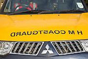 Coastguard  sign with mirror writing on hood of vehicle, England, UK