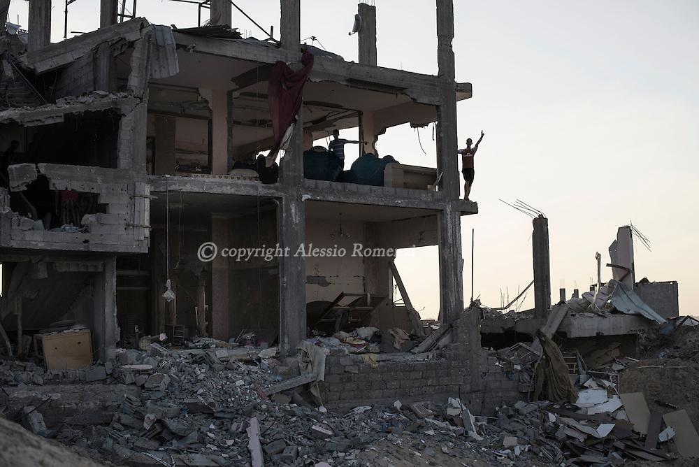 Gaza Strip, Gaza City: A Palestinian boy flashes the v of victory from a destroyed by strikes house in Al Shaaf neighbourhood during a 72 hours ceasefire on August 11, 2012. ALESSIO ROMENZI