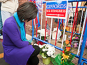 """15 JANUARY 2010 - TUCSON, AZ:    A woman prays at a memorial for the victims of the mass shooting in Tucson, AZ, Saturday, January 15, one week after the shooting. Six people were killed and 14 injured in the shooting spree at a """"Congress on Your Corner"""" event hosted by Arizona Congresswoman Gabrielle Giffords at a Safeway grocery store in north Tucson on January 8. Congresswoman Giffords, the intended target of the attack, was shot in the head and seriously injured in the attack but is recovering. Doctors announced that they removed her breathing tube Saturday, one week after the attack. The alleged gunman, Jared Lee Loughner, was wrestled to the ground by bystanders when he stopped shooting to reload the Glock 19 semi-automatic pistol. Loughner is currently in federal custody at a medium security prison near Phoenix. PHOTO BY JACK KURTZ"""