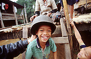 February 2005 - Quang Tri, Vietnam - In this Bru ethnic minority village a young boy has an old US Army helmet placed on his head. The helmet was found in the surrounding forests and is now used as a child's play toy. During the Vietnam War the Bru aided the North Vietnamese Army helping to fight, even with their primitive weaponry such as bows and arrows, and set traps in the surrounding jungle. Photo Credit: Luke Duggleby