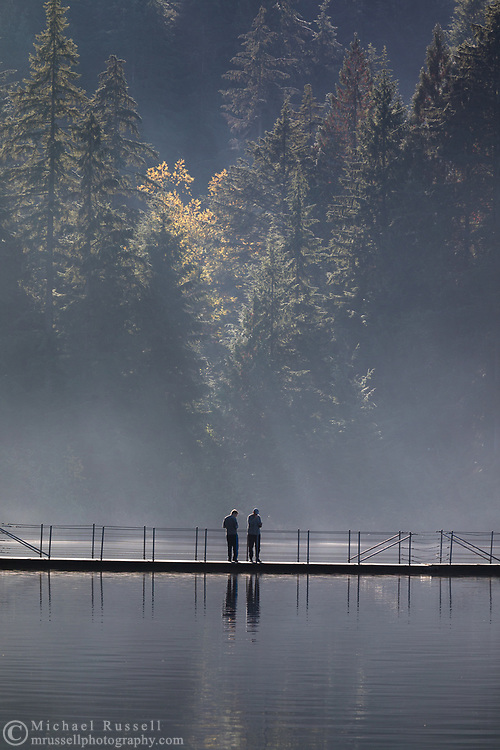 Two people enjoy the view from the floating bridge at Sasamat Lake in Port Moody, British Columbia, Canada.  White Pine Beach (popular during the summer months) is just around the corner from here and along with Sasamat Lake sits within Belcarra Regional Park.