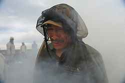 Dene First Nation Joseph Catholique stands in the smoke to get relief from the carnage of millions of black flies and mosquitoes. (Photo by Ami Vitale)