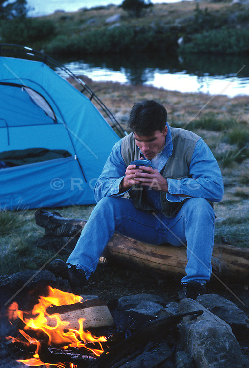 Man sitting by a camp fire drinking coffee