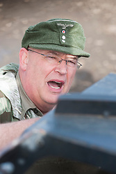 A reenactor portraying German officer wearing an M43 ski cap (Einheitsfeldm&uuml;tze) and splinter pattern camouflage smock speaks to an armored vehicle driver during preparation for a Battle reenactment on the Pickering Showground during the towns wartime weekend<br />