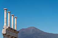 At Pompeii Archaeological Park, white marble columns or pillars appear against blue sky with Mt. Vesuvius in the background, Compania Region, Italy.