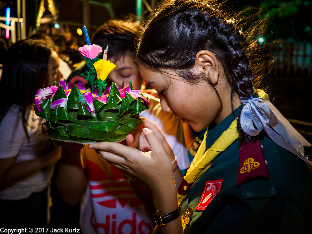"""03 NOVEMBER 2017 - BANGKOK, THAILAND: A Girl Scout prays before floating her krathong during Loi Krathong at Wat Prayurawongsawat on the Thonburi side of the Chao Phraya River. Loi Krathong is translated as """"to float (Loi) a basket (Krathong)"""", and comes from the tradition of making krathong or buoyant, decorated baskets, which are then floated on a river to make merit. On the night of the full moon of the 12th lunar month (usually November), Thais launch their krathong on a river, canal or a pond, making a wish as they do so. Loi Krathong is also celebrated in other Theravada Buddhist countries like Myanmar, where it is called the Tazaungdaing Festival, and Cambodia, where it is called Bon Om Tuk.     PHOTO BY JACK KURTZ"""