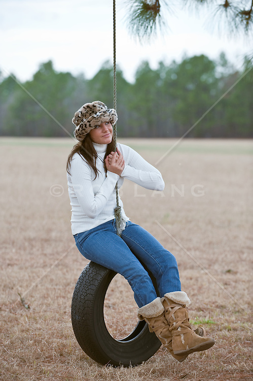 Young woman in a fur hat sitting on a tire swing