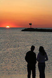Couple watching sunset in New Buffalo, Michigan