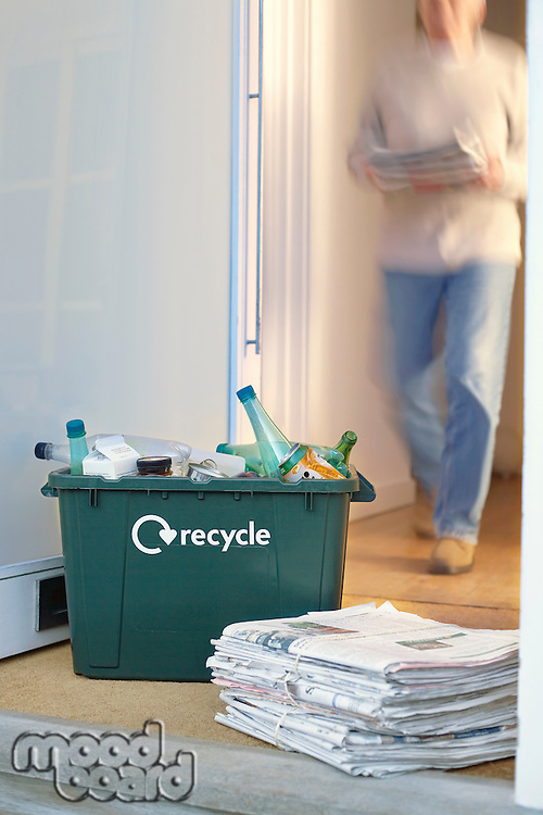 Recycling container and pile of waste paper on floor woman walking in background (motion blur)
