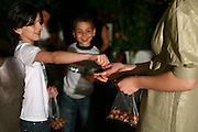 """An israeli family attending a """"Seder"""",  the traditional passover dinner,  and reading the """"Hagada"""" (the story of israeli's exodus from Egypt)  during the evening. Children are playing """"Odd or Even"""" (""""zug or peret"""") with hazelnuts, a passover traditonal game."""