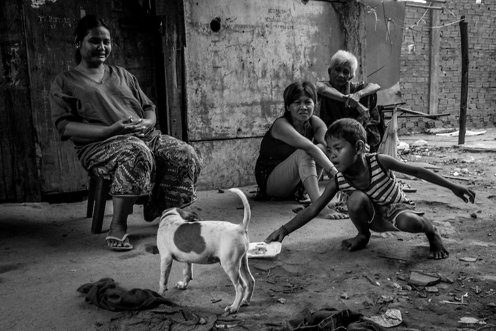 A young boy feeds the remains of his lunch to a dog in Borei Keila. The community of Borei Keila in Phnom Penh was once home to hundreds of families before land developer Phanimex bought the property rights to the area and forcefully evicted the residents who refused to accept their compensation package. Those who remained were forced to squat in the remains of the buildings, living in slum-like conditions and without access to plumbing or public electiricity.