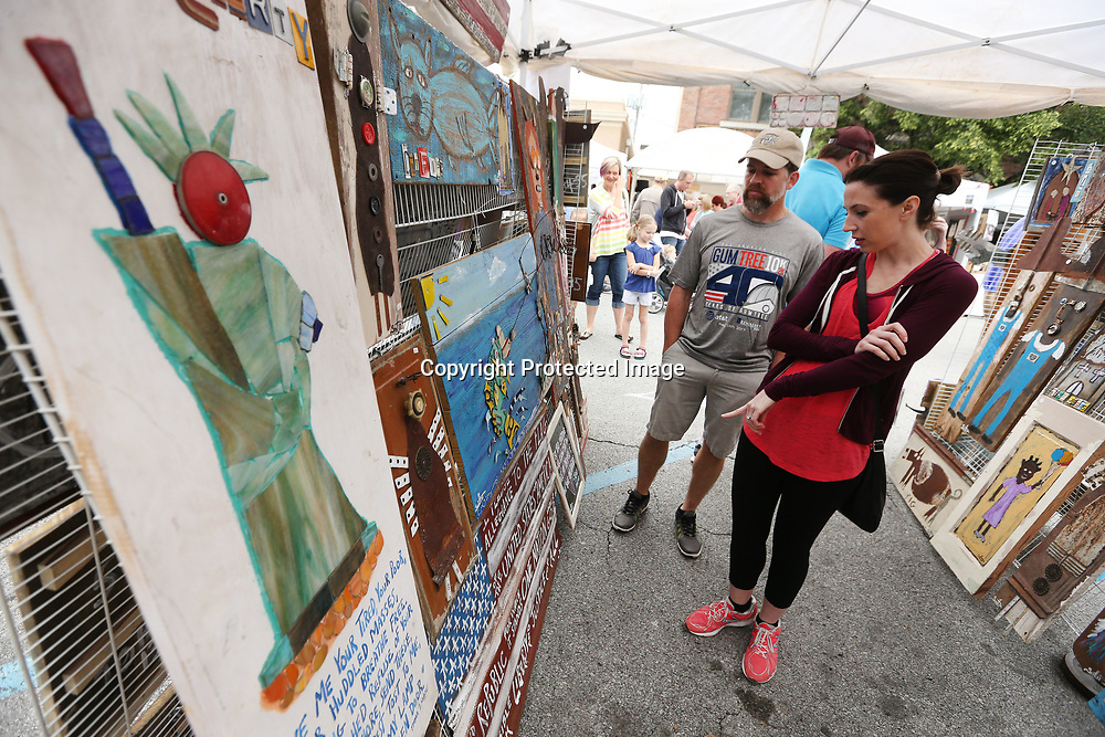 Bart and Charlcy Hollingsworth, from Hamilton Alabama, look over art work created by Scott McQueen as they shop around the different artist booths at the GumTree Festival Saturday in Downtown Tupelo. McQueen is a folk artist based in Northport Alabama.