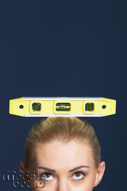 Woman balancing spirit level on her head against dark background high section