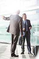 Businessmen talking while waiting for taxi in the airport