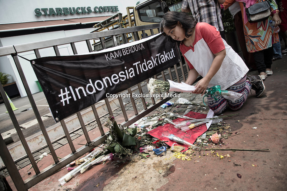 Jakarta, Indonesia 17 January 2016 : <br /> <br /> A woman puts flowers in front of the bombed starbucks coffee to pay tribute to the victim. Jakarta back to normal again after the fatal attack at Starbuck Coffee at Thamrin Street. People still visiting to the bomb site to take photos and condemn to the terrorist action.<br /> ©Exclusivepix Media