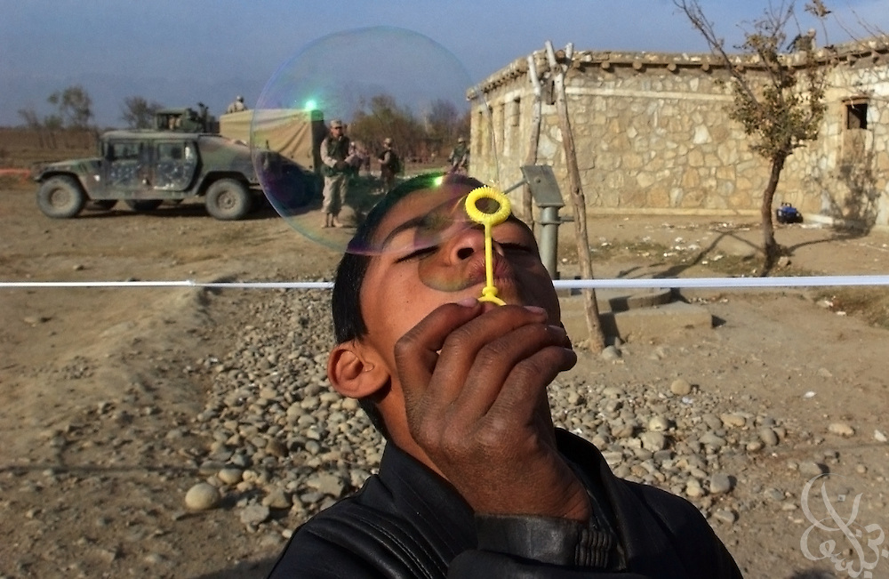 """An Afghan boy blows bubbles given to him by U.S. Army troops (seen in the background) December 3, 2002 during a U.S. military civil humanitarian mission in the village of Tadokhile in central Afghanistan. The mission provided more than a hundred Afghan men, women and children from the village with free medical care and basic dentistry as part of """"Operation Enduring Freedom""""."""