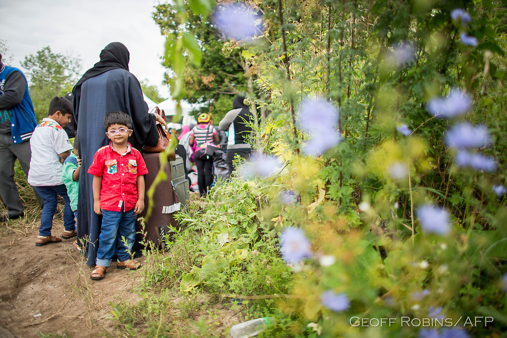 A long line of asylum seekers wait to illegally cross the Canada/US border near Champlain, New York, August 6, 2017. In recent days the number of people illegally crossing the border has grown into the hundreds.