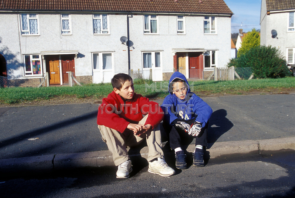 Two kids sitting on the curb on a residential street
