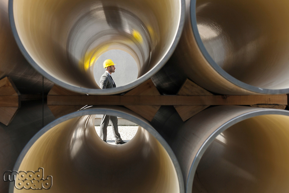 Full length side view of young male architect walking by stacked pipes at construction site