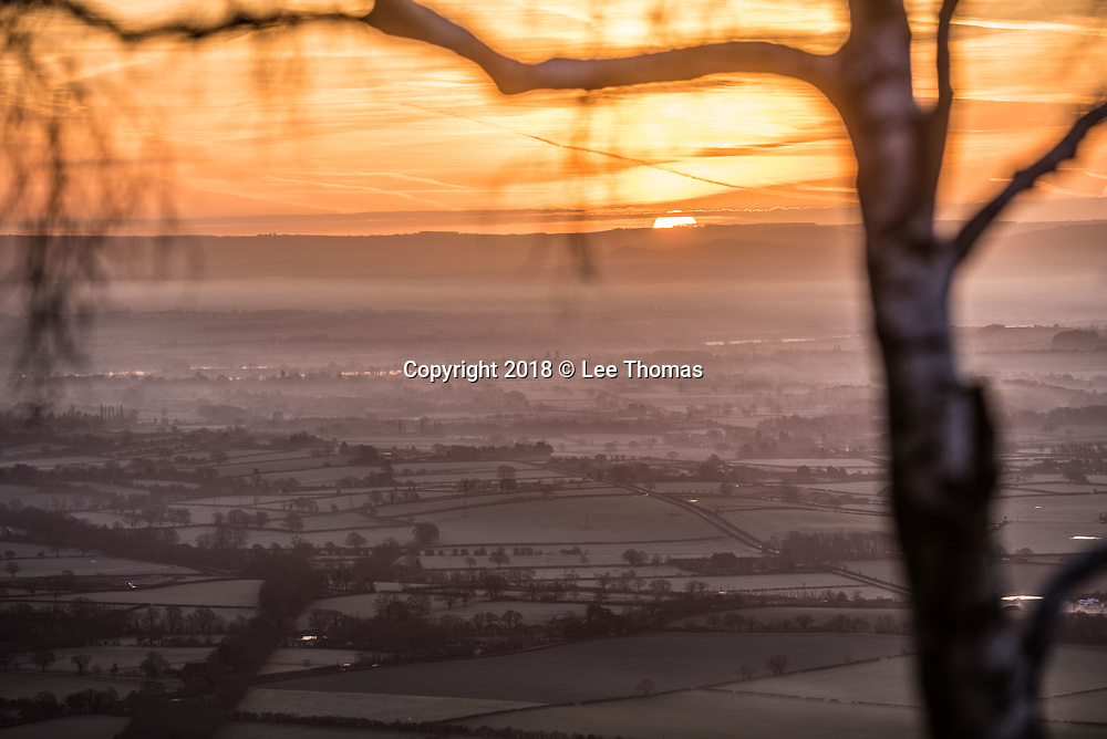 Malvern Hills, Worcestershire, UK. 30th January 2018.  A cold and frosty sunrise on the Malvern Hills. Pictured: Sunrise appears across a misty Severn plain. // Lee Thomas. Tel. 07784142973. Email: leepthomas@gmail.com www.leept.co.uk (0000635435)