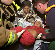Green Valley, Arizona, USA, paramedics/firefighters move Josemara Aquino, 3, an illegal immigrant from Mexico, from her mother's arms to a backboard for transport to a Tucson hospital.  The girl was among 41 illegal immigrants packed into an extended cab pickup truck that rolled when the smuggler attempted to flee Border Patrol agents after being spotted by a helicopter near Arivaca.  As the truck increased in speed, ground units pulled back, but the chopper continued to follow the vehicle.  Five helicopters made a total of 6 trips to transport the most seriously injured to Tucson.  14 ambulances transported others from the scene on Old Nogales Highway, about 18 miles south of downtown Tucson.  The driver/smuggler was taken into custody after he tried to flee.  About 10 children were in the vehicle and were stuffed into the front seat and extended cab.  The others were stacked in the bed of the truck.  The rollover took place on March 14, 2002 near Sahuarita, Arizona.