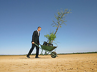Businessman pushing wheelbarrow full of plants in desert