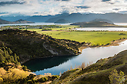 Morning light illuminates green farmland surrounded by the many waterways of Lake Wanaka.