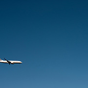 A United passenger jet comes in to land, flying against a clear blue sky.