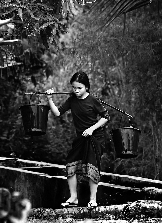 A girl carrying water home in Luang Prabang, Laos.