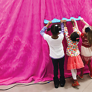"March 10, 2012 - New York, NY : Museumgoers, from left, Tristen Duncan, 6, Jordyn Taylor, 4, and Ella Gershon, 5, use oversized combs to rake the pink faux fur of Misaki Kawai's giant dog as they explore Kawai's ""Love from Mt. Pom Pom,"" exhibit, at the Children's Museum of the Arts in the south village  on March 10. CREDIT: Karsten Moran for The New York Times"