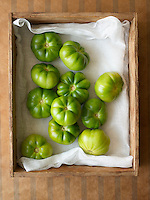 Green tomatoes in wooden box overhead view