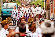 Apr. 25 -- UBUD, BALI, INDONESIA:  Mourners join the funeral procession for Cokorde Gede Raka, a member of Ubud's royal family Sunday, Apr. 25. Balinese are Hindus and cremate their dead. Balinese funerals are elaborate - and expensive - affairs. A funeral for one person costs a minimum of 45 million rupiah (about $5,000 US). The body is placed into the bull's body at the cremation and cremated in the bull. The funeral pyre is burnt adjacent to the bull. That is what a family may earn in two to three years. The result is that only the rich can afford formal cremations. The body (in the casket) is placed in the top of the funeral pyre and the procession takes the body to the cremation site. The funeral pyre, and the body, are spun at intersections to confuse the spirits so the soul doesn't try to return to its home and to confuse evil spirits.    PHOTO BY JACK KURTZ