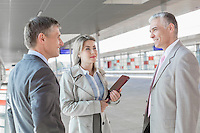 Businessman communicating with colleagues on train platform