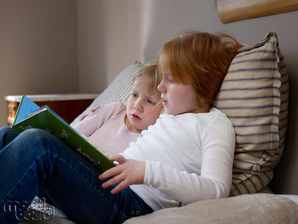 Two sisters sit reading on a single bed