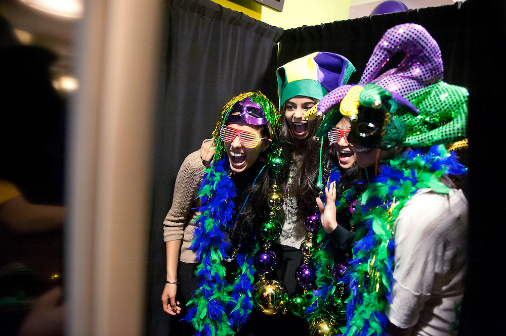 February 11, 2013 - From left, second-year College of Science students Gagan Singh, Khushi Chhangani, Aisha Sajjad and Meera Shah pose in a photo booth during the 12th Annual Mardi Gras Celebration in Levine Marketplace, which featured special food, caricature artist, henna tattoo station, the Hot Tamales Brass Band and contests in pancake stacking, cereal eating and finding candies in pans of whipped cream without the use of one's hands.